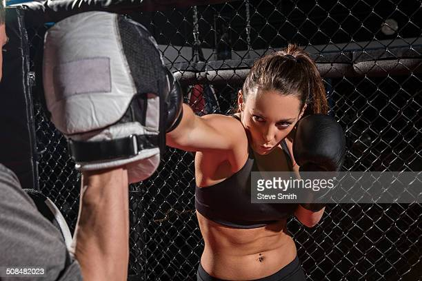 Caucasian fighter working with trainer in gym