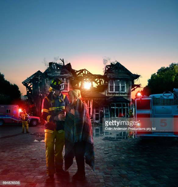 Caucasian firefighter comforting woman at burned house