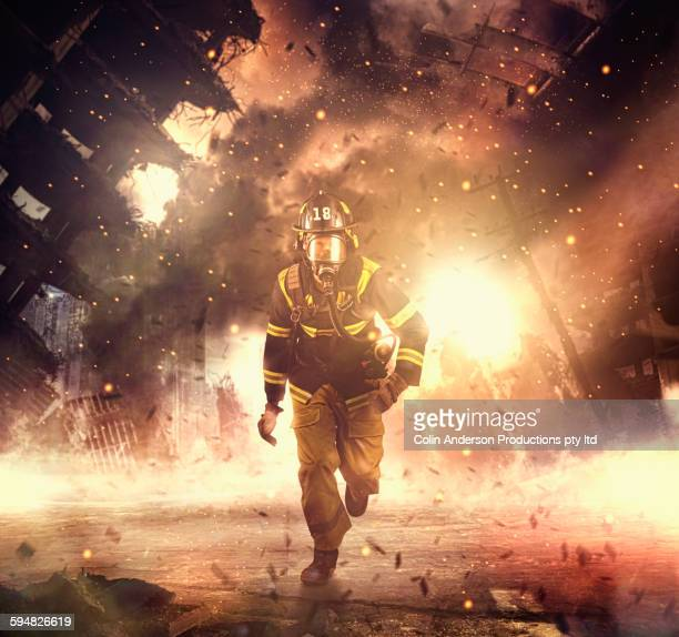 Caucasian firefighter running in burning building