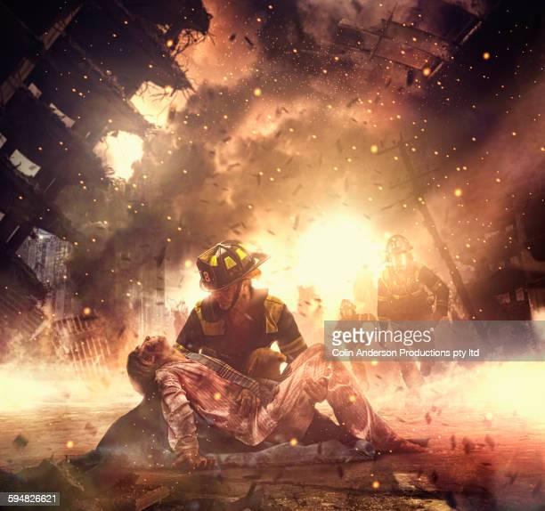 Caucasian firefighter saving boy in burning building