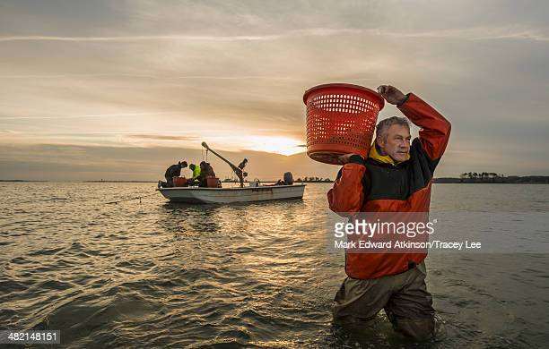 Caucasian fisherman carrying basket in water