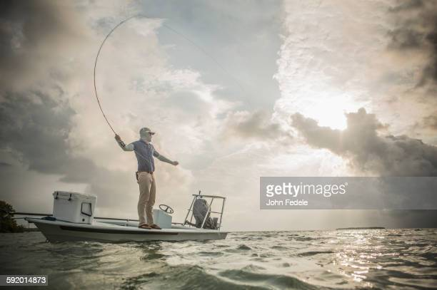 Caucasian fisherman casting line from boat