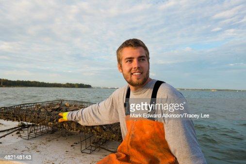 Caucasian fisherman holding net on boat