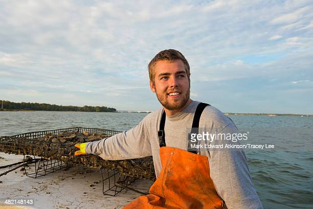 Caucasian fisherman holding net on boat