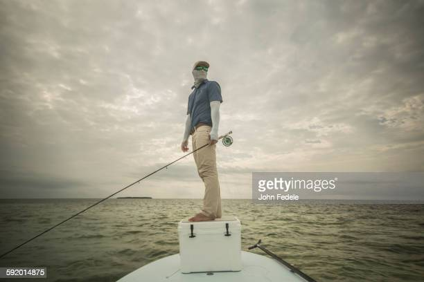 Caucasian fisherman standing on boat