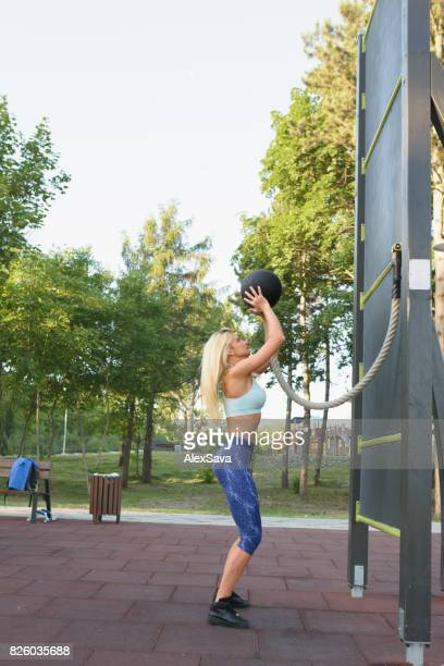 Caucasian fit woman doing calisthenics exercises with dumbbell outdoor