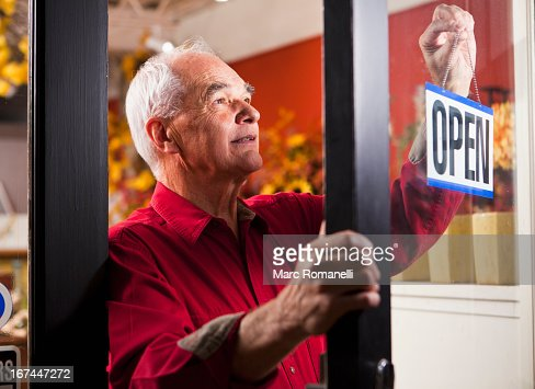 Caucasian florist hanging open sign in shop : Stock Photo