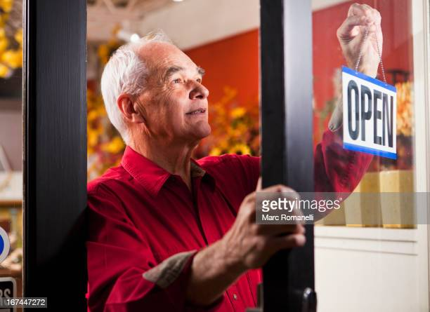 Caucasian florist hanging open sign in shop