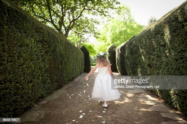 Caucasian flower girl sprinkling petals in garden