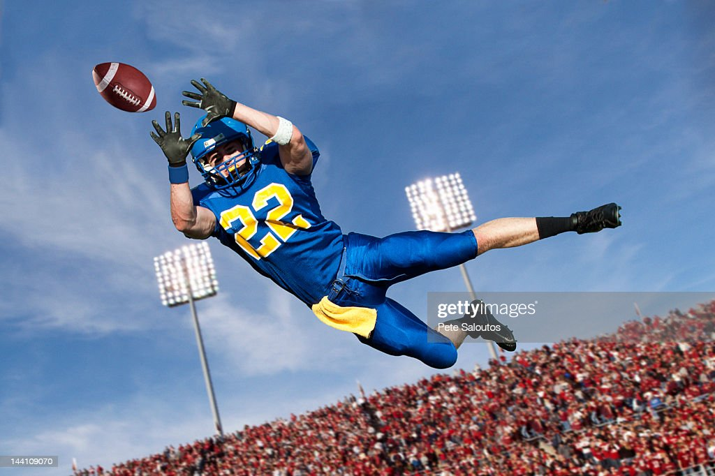 Caucasian football player catching ball : Stock Photo
