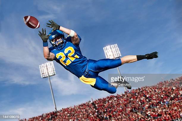 Caucasien attraper un ballon de football américain