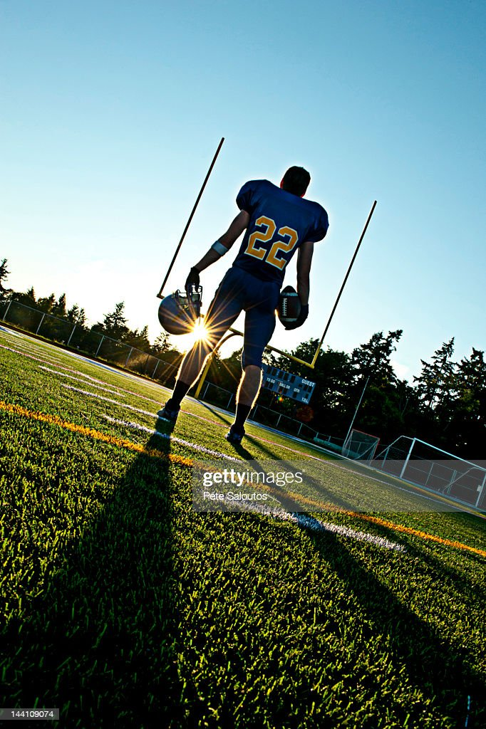 Caucasian football player holding ball : Stock Photo