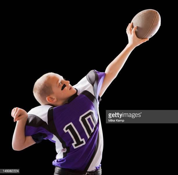 Caucasian football player holding up football