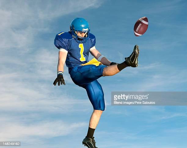 Caucasian football player kicking football