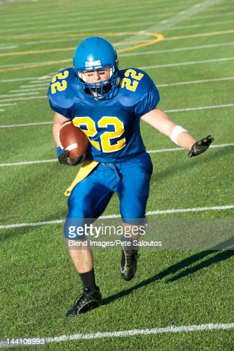 Caucasian football player running with ball : Stock Photo
