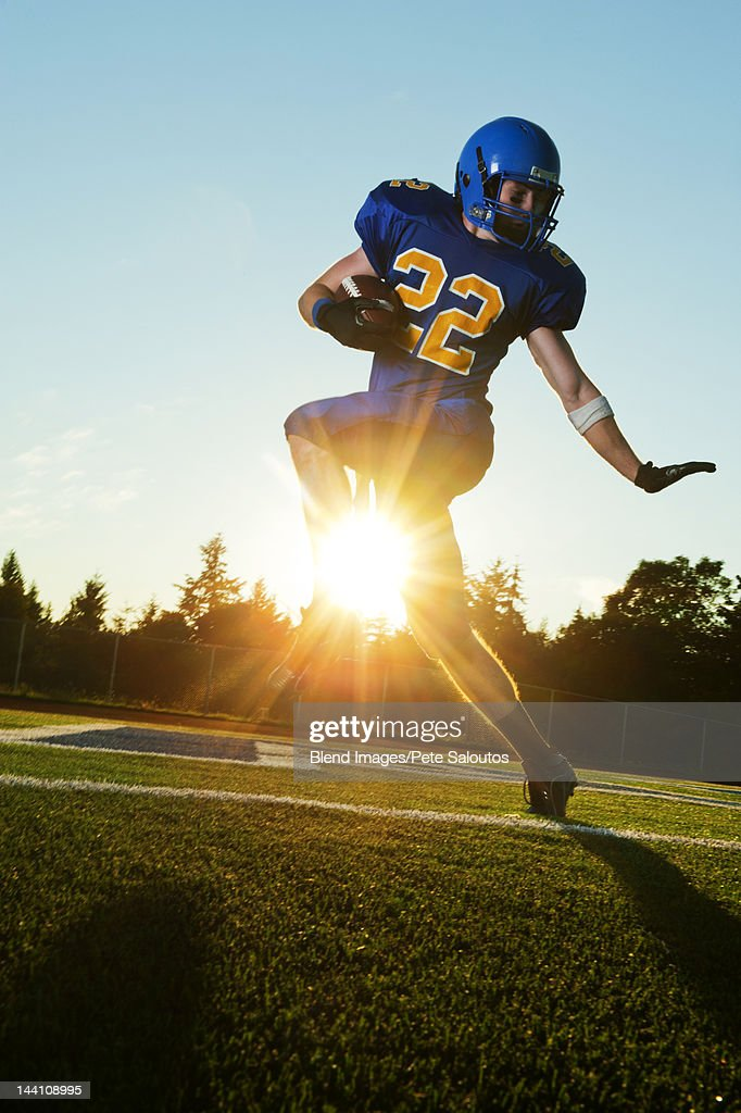 Caucasian football player running with ball