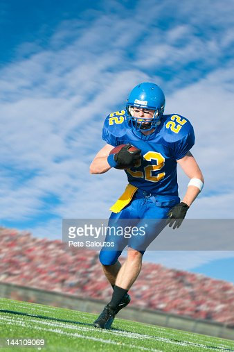 Caucasian football player running with ball : Stock Photo
