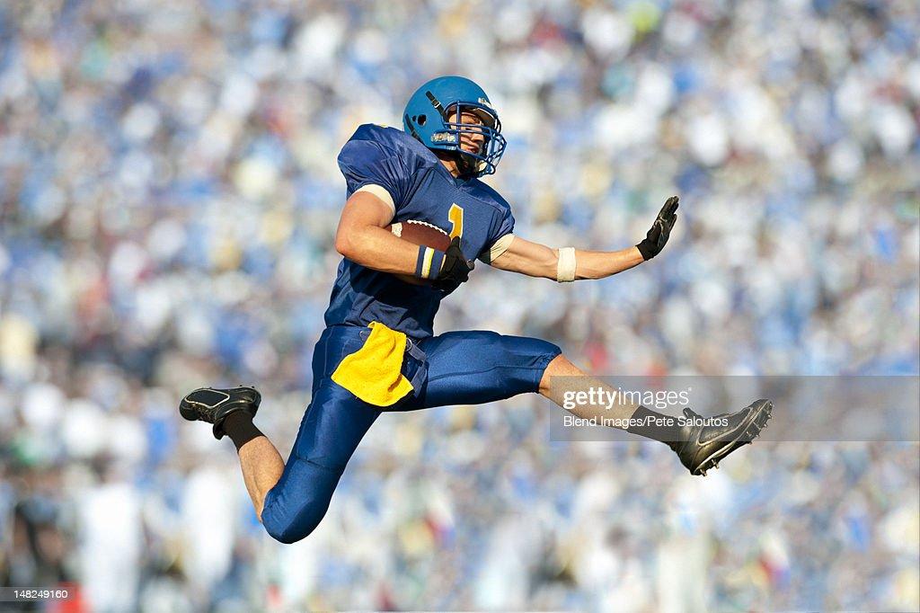Caucasian football player running with football