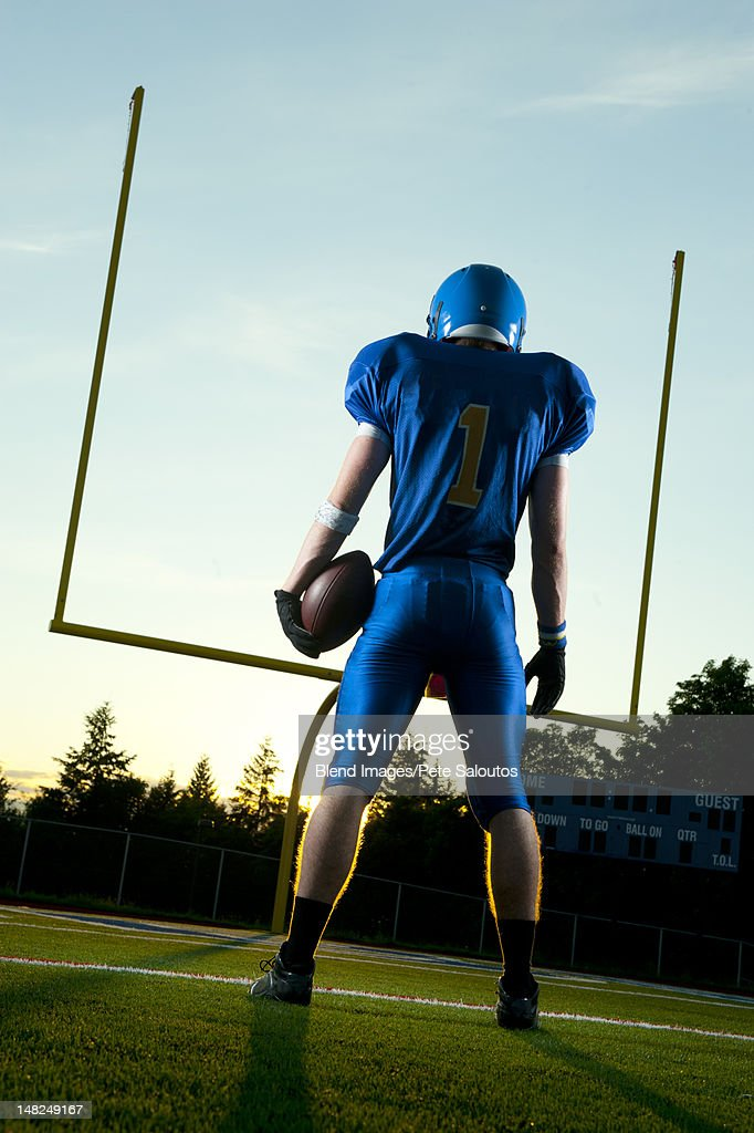 Caucasian football player standing with football