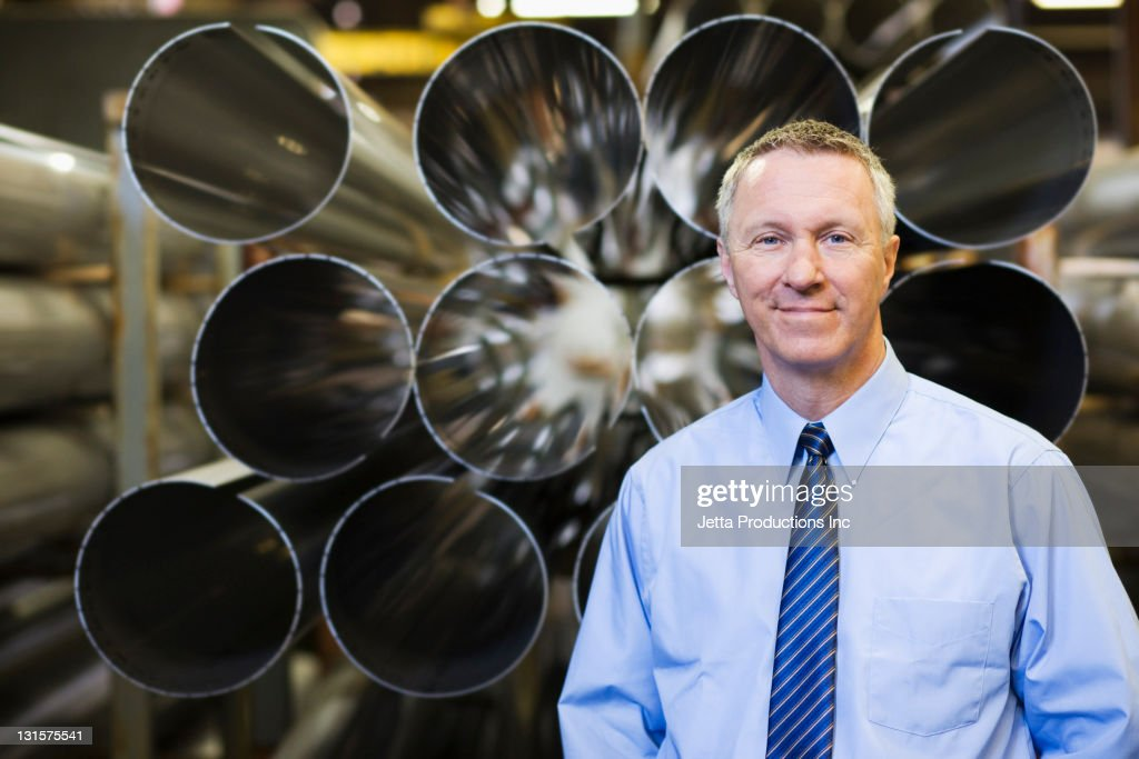 Caucasian foreman standing near pipes in factory : Stock Photo