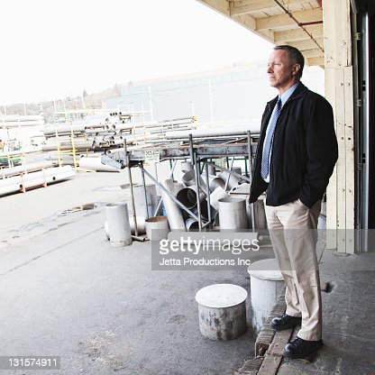 Caucasian foreman standing on factory loading dock