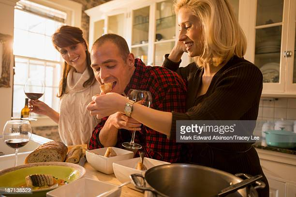 Caucasian friends eating together in kitchen