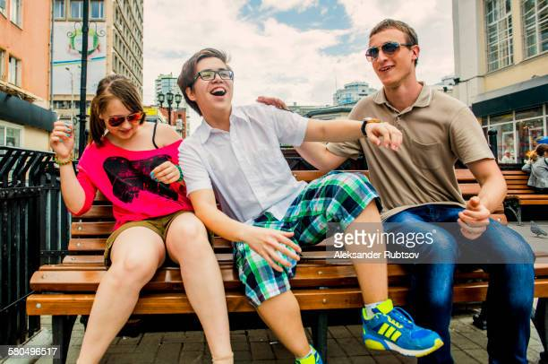 Caucasian friends playing on city bench