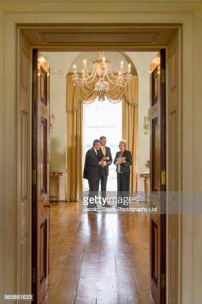 Caucasian friends talking in formal mansion parlor