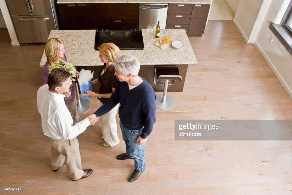 Caucasian friends talking together in modern kitchen