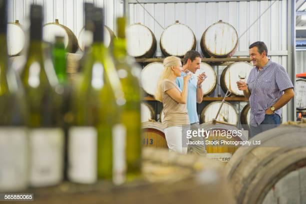 Caucasian friends tasting wine in winery