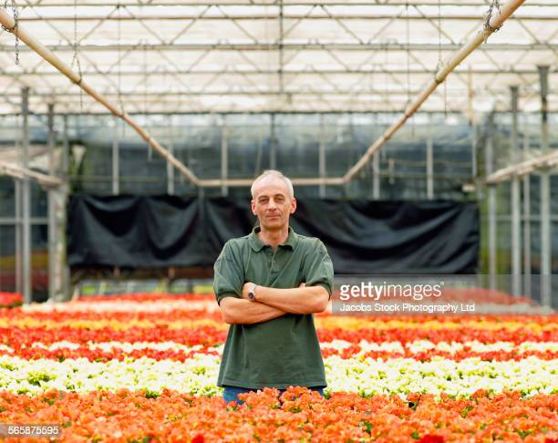 Caucasian gardener standing with flowers in greenhouse