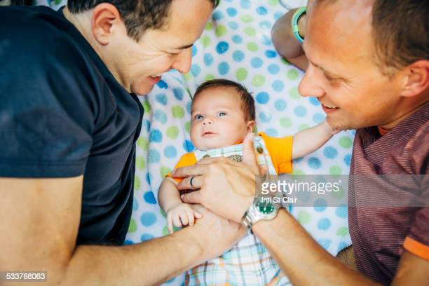 Caucasian gay couple cuddling baby boy