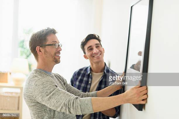 Caucasian gay couple hanging picture on wall