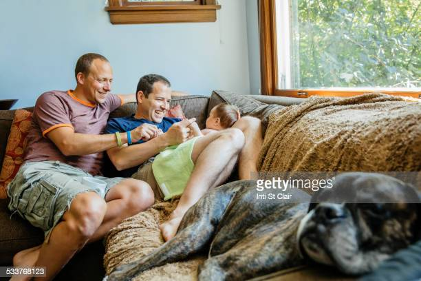 Caucasian gay couple playing with baby boy on sofa