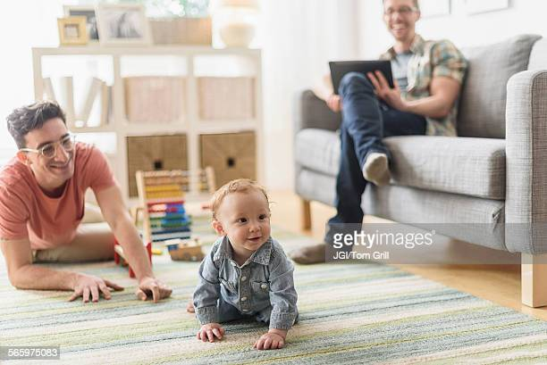 Caucasian gay parents relaxing with baby