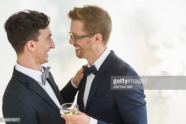 Caucasian gay grooms hugging at wedding