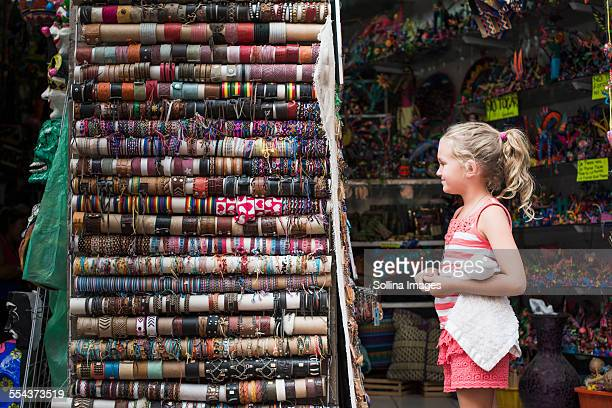 Caucasian girl admiring woven bracelets for sale in market