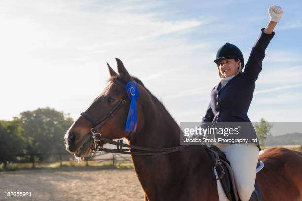 Caucasian girl and horse winning equestrian competition