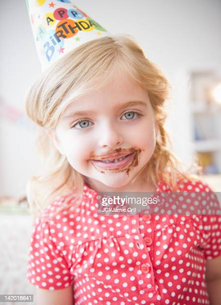 Caucasian girl at birthday party with chocolate on her face