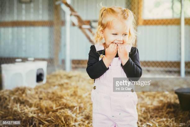 Caucasian girl biting fingers in barn