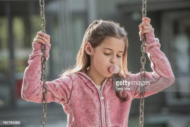 Caucasian girl blowing bubble on swing