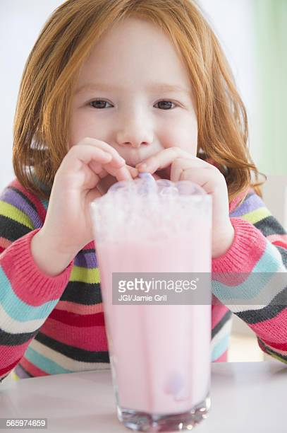 Caucasian girl blowing bubbles in strawberry milk