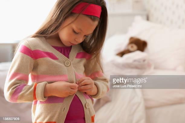 Caucasian girl buttoning her sweater
