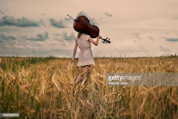 Caucasian girl carrying cello on shoulder in rural fieldCaption