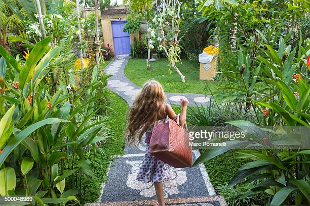 Caucasian girl carrying purse on stone backyard steps