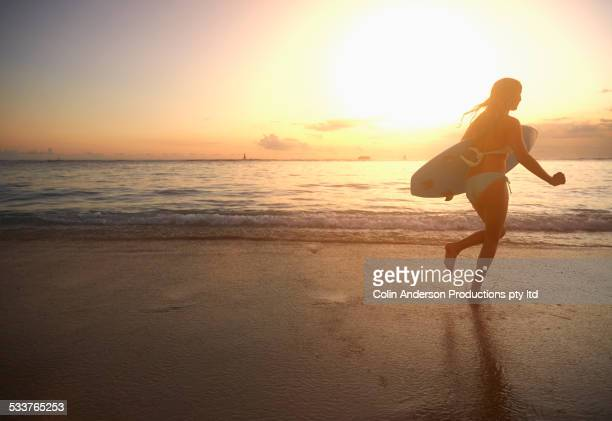 Caucasian girl carrying surfboard on beach