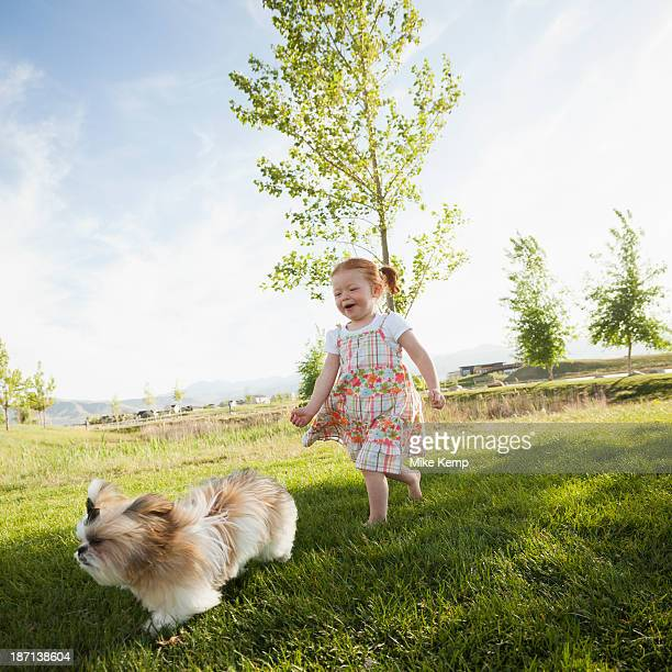 Caucasian girl chasing dog in grass