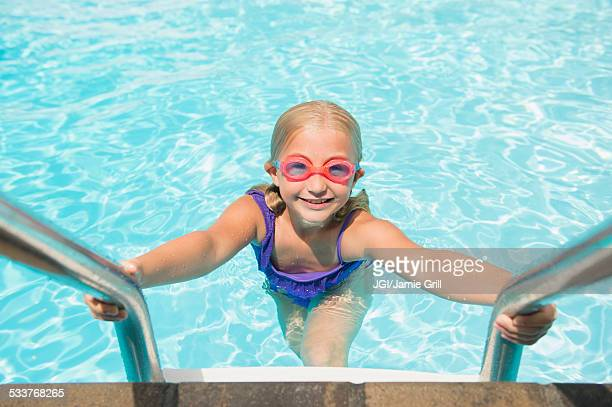 Caucasian girl climbing out of swimming pool