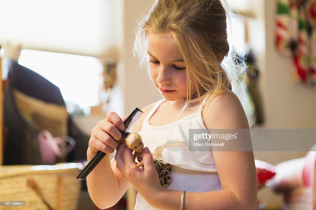 Caucasian girl combing doll's hair