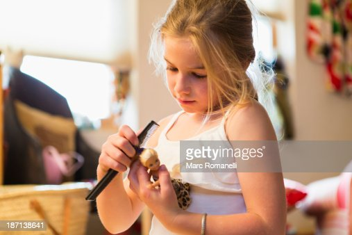 Caucasian girl combing doll's hair